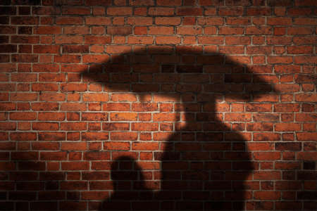 Autumn rainy day. Two people cast a shadow on the old red grunge brick wall texture background Stockfoto