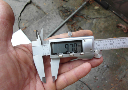 Measure caliper. Very small size. Hand in the frame. Close-up meter.