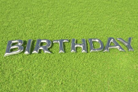 BIRTHDAY word made with silver foil balloons on green grass Фото со стока - 150499485