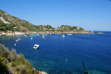 A bay in Giglio Island: the rocky coast and boats off the coast