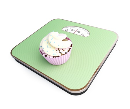 bathroom scale with the cupcake    on a white background photo