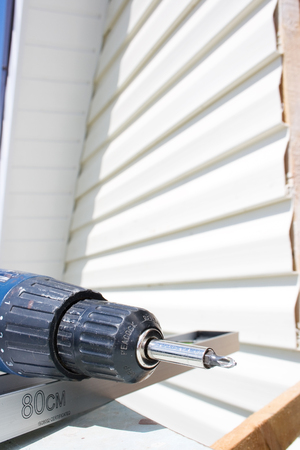 Tools for mounting the siding, screwdriver and level Stock Photo