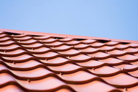 undulate: Red roof of metal roofing on the sky background