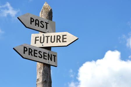 Wooden signpost - past, future, present