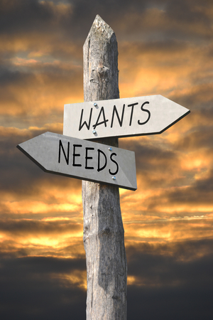 wants: Wants and needs signpost Stock Photo
