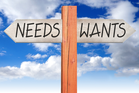 Wants or needs - wooden signpost Stock Photo