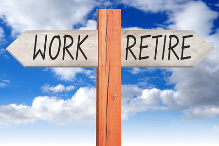 retire: Work or retire - wooden signpost