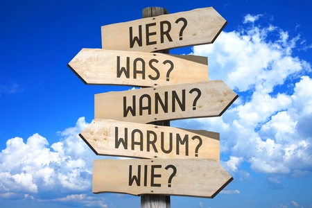 when: Wooden signpost - questions in German Stock Photo