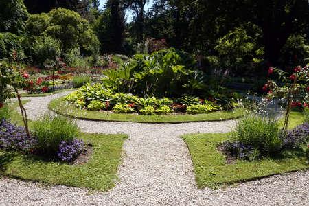 Path in garden, flowers, grass Foto de archivo - 152668704