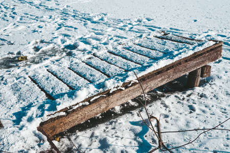 Footbridge and frozen lake covered with snow in winter