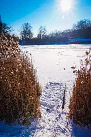 Frozen pond covered with snow in winter