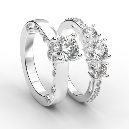 3D illustration two white gold or silver rings with diamonds with reflection on a grey background