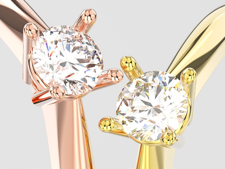 3D illustration two close up yellow and rose gold traditional solitaire engagement diamond rings on a gray background Stock Photo