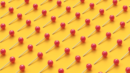 Many sweet lollipops arranged in rows on yellow background