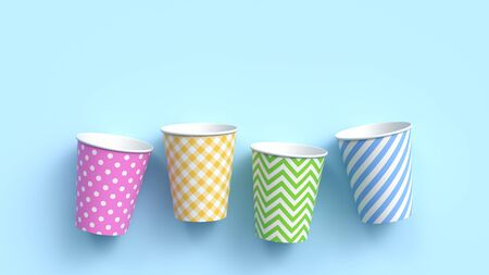 Four paper cups with different colorful patterns on blue pastel background