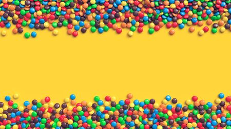 Double border of colorful coated chocolate candies on yellow background Archivio Fotografico