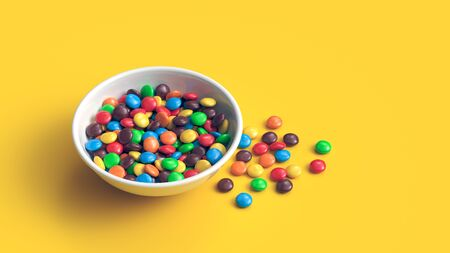 Colorful coated chocolate candies in white bowl isolated on yellow background Zdjęcie Seryjne