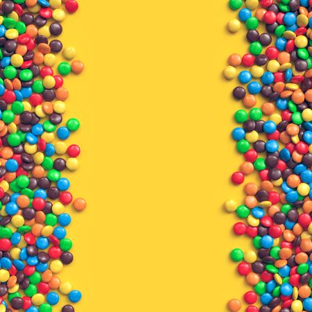 Double border of colorful coated chocolate candies on yellow background Zdjęcie Seryjne
