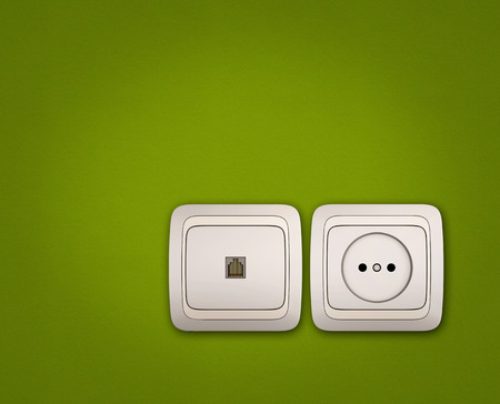 Computer and electrical outlets on green wall background photo