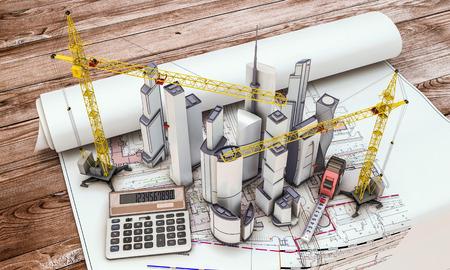 設計図の上にクレーンで建設中のビル
