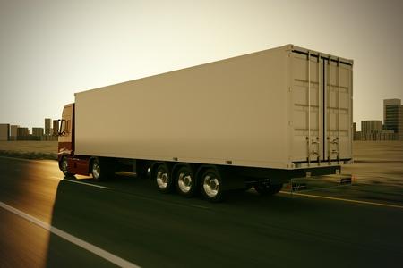 Grand camion de livraison se déplace rapidement sur la route pendant le coucher du soleil