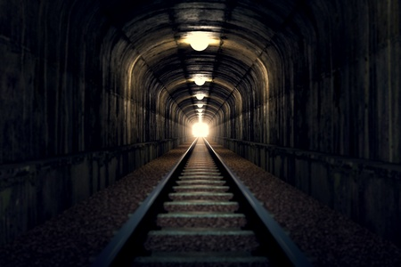 the end: A railroad tunnel with a light at the end.  Stock Photo