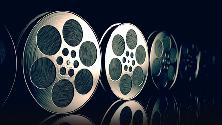 film reel: Row of new reflective film spools with tape on dark background.