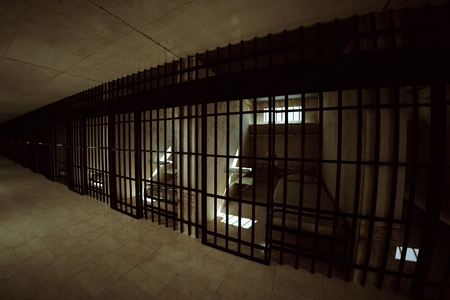 Render of prison corridor with locked cells for one person with bed, sink, toilet and chair. Dark atmosphere.
