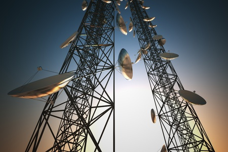 Two tall telecommunication towers with antennas in twilight sky.