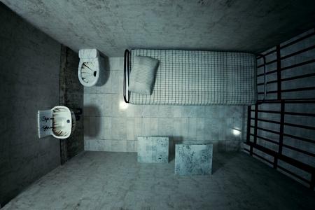 Pohled shora na uzamčené staré vězeňské cely pro jednu osobu s postelí, umyvadlem, WC a židle. Tmavě atmosféra.