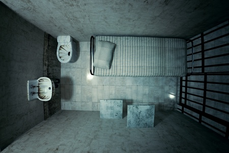 wall bars: Top view of locked old prison cell for one person with bed, sink, toilet and chair. Dark atmosphere.