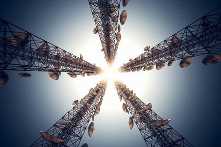 Five tall telecommunication towers with antennas on blue sky. View from the bottom.