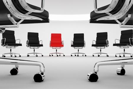 Rode stoel tussen reguliere, zwarte bureaustoelen Stockfoto
