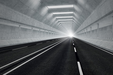 tunnel view: Driving through an underground car tunnel. Daylight seeps in through the end of the tunnel. May represent travel, speed, transportation or urban communication.
