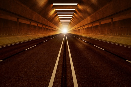 Driving through a dark car tunnel. Dimmed lights with orange tint. View from the inside. May represent travel, speed, transportation or urban communication. Stock Photo