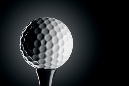 Closeup on a single white golf ball isolated on a dark background.