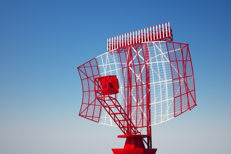 An airport surveillance radar on a bright blue sky background. Front view. photo