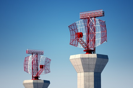 Two airport surveillance radars on a bright blue sky background, situated on a terminal area.