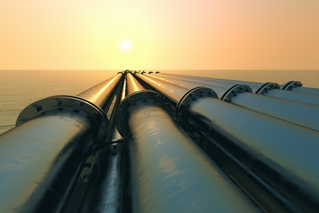 Tubes running in the direction of the setting sun. Pipeline transportation is most common way of transporting goods such as Oil, natural gas or water on long distances.  Stock Photo