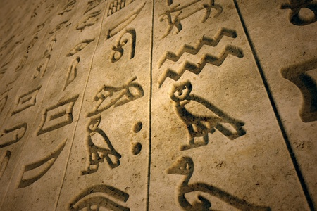 hieroglyphs: Stone wall with ancient hieroglyphs engraved on. Bottom shot. Hieroglyphs is a writing system known as the oldest  alphabet.