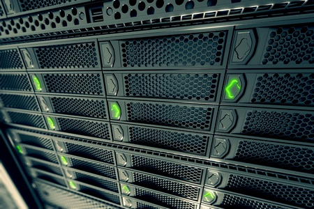 Closeup on data servers while working. Green LED lights are flashing. Image can represent cloud computing, information storage, etc. or can be the perfect technology background.