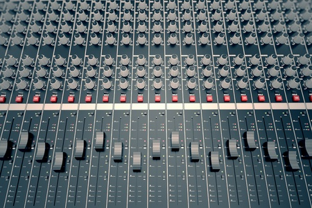 Top shot of a mixing console, equipped in various sliders, switches and adjusters. It is used for audio signals modifications to achieve the desired output. Applied in recording studios, broadcasting, television and film post-production.