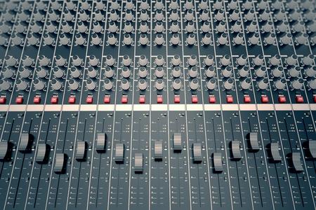 Top shot van een mengpaneel, uitgerust in verschillende sliders, schakelaars en regelaars. Het wordt gebruikt voor audiosignalen wijzigingen van de gewenste uitvoer te bereiken. Toegepast in opnamestudio's, omroepen, televisie en film postproductie.