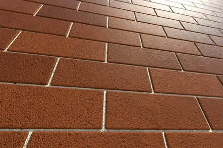regularly: Closeup on a regularly tiled red bricks  Might be used as a background, pattern or building facade illustration  Stock Photo