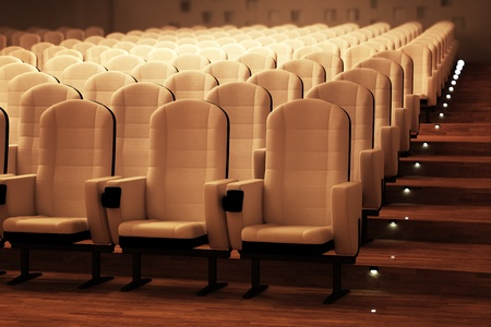 Rows of comfortable white leather seats and a wooden floor in a large empty cinema. photo