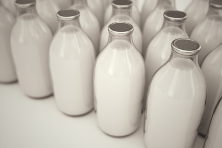 Rows of old-fashioned glass bottles filled with milk on a white backround. Perfect for any health or natural nutricion realted purposes.
