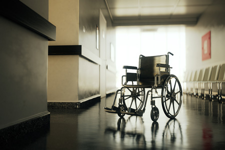 Standard manual wheelchair standing in empty hospital corridor