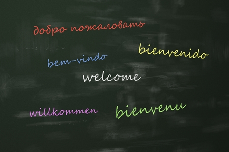 Language learning concept with a class blackboard covered in colorful text depicting the word - Welcome - in multiple different international languages with random orientation