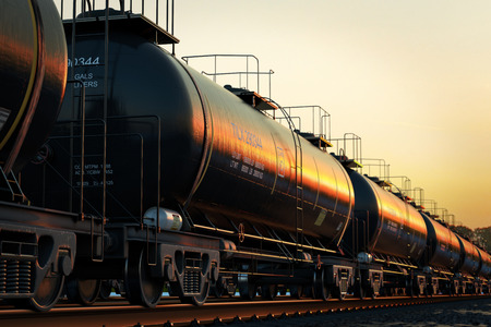 railroad transportation: Transportation tank cars with oil during sunset.
