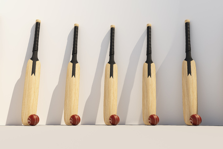 Cricket bat with ball at the white wall Stock Photo